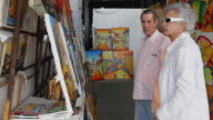 MS ZO Men looking at paintings in artist's shop / Havana, Cuba