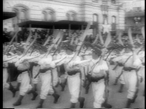 PAN men marching carrying skis in parade honoring Juan Peron / Peron in background / Buenos Aires