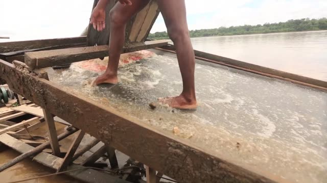 TS Men mine for gold on a river barge The region of Madre de Dios in SouthEastern Peru has been devastated by illegal gold mining it has a...