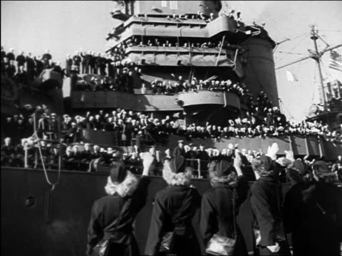 B/W 1945 men on deck of military ship waving to women in foreground / WW II homecoming / documentary
