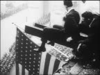 B/W 1918 2 men on metal beam watch Victory Parade on Fifth Avenue below at end of World War I / NYC