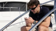 Men on the phone on yacht