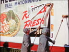 1941 REAR VIEW 2 men pasting up 'really fresh' mayonnaise billboard sign / Chicago / industrial