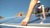 CU Men picking up and placing down the solar panel on frame / Greenfield, Massachusetts, USA