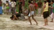 Men play Bangladesh's national sport, Kabaddi, on sand, watched by spectators.
