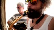 Men playing guitar and saxophone