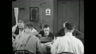 Men pray before spearing food frustrating a hungry Buster Keaton