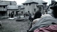 Men push a cart bearing a dead body through a village.