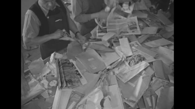 Men push carts loaded with confiscated papers during Word War II with policeman escorting / striped US Mail bags labeled ÒforeignÓ / men at long...