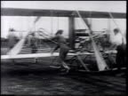 Men pushing 'Wright Flyer' Army Signal Corps Airplane No 1 'Benny' Foulois w/ unidentified man next to aircraft biplane taking off flying [VO Retired...