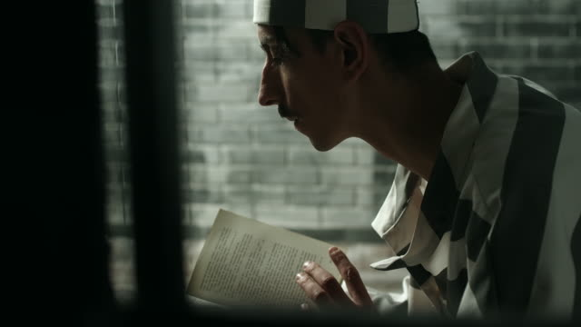 Men reading book at prison cell