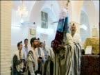 Men reciting Hebrew prayers in synagogue as ancient Torah scrolls are paraded Iran