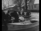 Men remove bundles from rowboat in foreground as boat with passengers approaches in flooded street during Ohio River Valley flood / girl winces as...