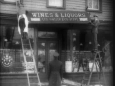 B/W 1920 men removing 'Wine Liquors' sign from store as policeman watches / Prohibition / newsreel