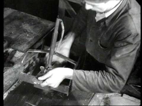 Men repair wornout clogs by placing new wooden soles on them in workshop / Bergen op Zoom Netherlands