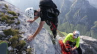 Men rock climbing in the mountains.  - 1920x1080