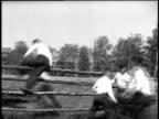 men running across field jumping over a fence others helping / men scrambling over trees / men climbing a hill