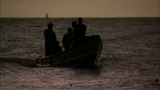 Men sail across sea towards shoreline fishing nets in small fishing boat Available in HD.