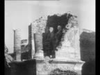 Men shovel volcanic ash from Mount Vesuvius eruption as ruined buildings stand in background / destroyed stone building at Pompeii with statues...