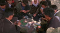 Men sit in circle playing cards Available in HD.