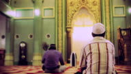 Men sit in prayer at a mosque.