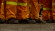 Men stand around in orange overalls with yellow stripes. Available in HD.