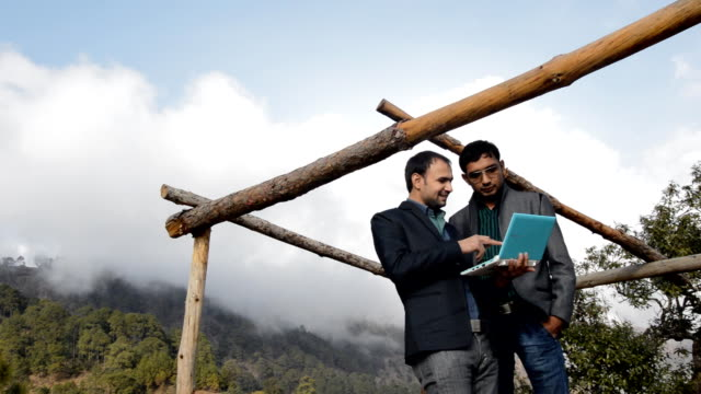 Men Standing in Mountains Holding Laptop
