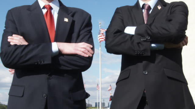 CU Men standing with arms crossed in front of American flags / Washington, DC, USA