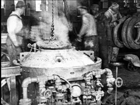 B/W 1925 men stirring boiling vat in Goodyear tire factory / industrial