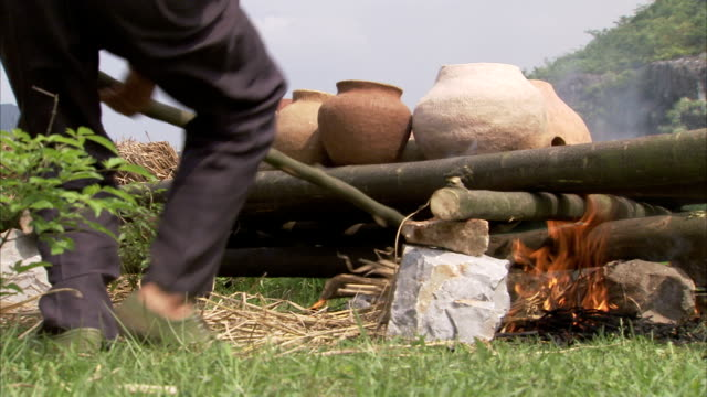 Men stoke flames to fire clay pots. Available in HD