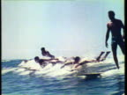 1953 WS PAN Men surfing in ocean, Dog also surfs along with them / Hawaii, USA / AUDIO