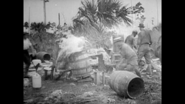 Men take axes to whiskey barrels and smashing them during Prohibition Whiskey barrels smashed up during Prohibition on January 01 1920