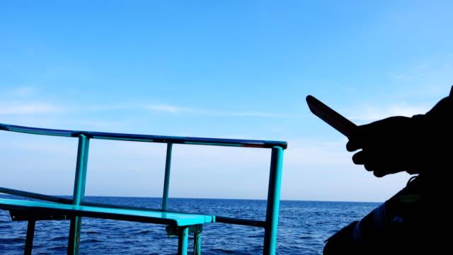 Mannen gebruiken de smartphone op de boot.