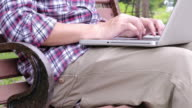 Men using a laptop at public park