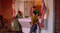 Men visit a butcher shop in Morocco. Available in HD.