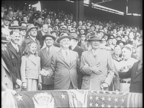 Men walk up ramp into Griffith Stadium / Panning shot of stadium crowd / President Roosevelt greets managers from the Washington Senators and New...