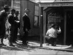 B/W 1927 PAN men watch as man writes stock market prices on chalkboard / Nevada / newsreel