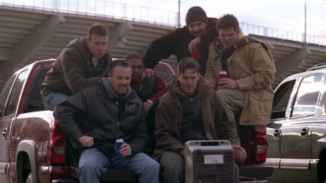 Men watching football game on TV and cheering at tailgate party outside stadium