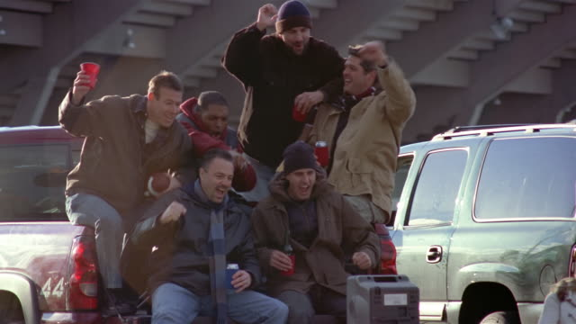 Men watching football game on TV and cheering at tailgate party outside stadium / bored wives sitting in folding chairs next to truck