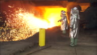 Men wear protective suits next to a flaming furnace.
