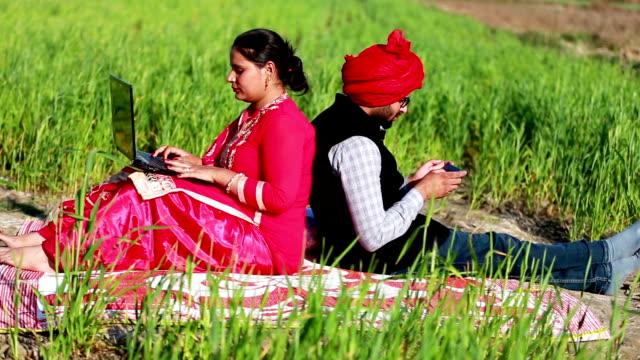 Men & women portrait in the green field using laptop & Smartphone