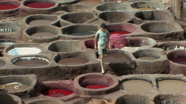 WS HA TD Men working around stone vessels for dying skins in tannery, Fez, Morocco