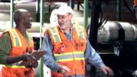 Men working in carpet warehouse talking, forklift