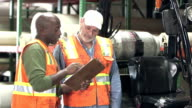 Men working in carpet warehouse talking, with clipboard