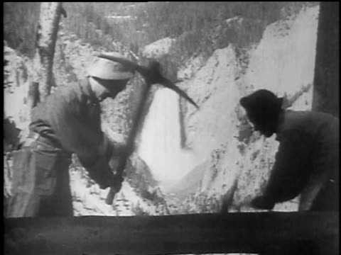 men working on a hiking trail overlooking a waterfall / men working at the foot of a waterfall / Old Faithful Geyser erupting