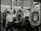 Men working on incomplete airplane engines in factory CU Newspaper clippings 'Aircraft Strike Ties up Orders of $50 000 000' 'CIO Strike Shuts War...