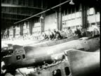 Men working on Junkers JU88 airplanes lined up side by side Men working on airplane bodies Luftwaffe fighter airplanes lined up outside factory PAN...