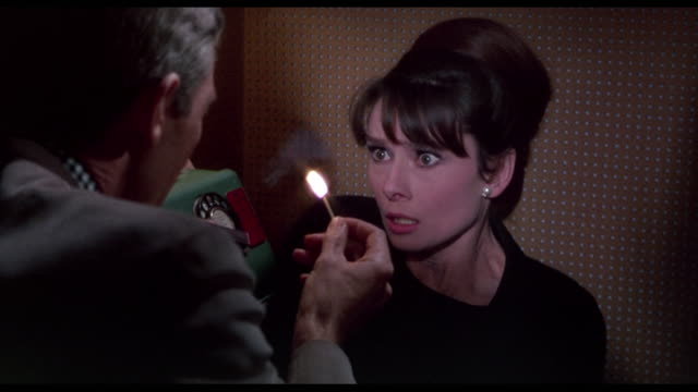 Menacing man (James Coburn) threatens scared woman (Audrey Hepburn) with lit matches in telephone box