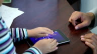 Men's and children's hands play on the tablet