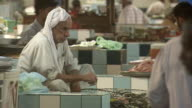 MS Merchant sitting in ceramic tiled booth with basket of fish for sale at indoor fish market / Manama Bahrain